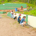 """Volunteer painters brighten the retaining wall at Babb's Beach as part of a big work crew on May 21. From far to near: Wendy LaMontagne, Kaci Seibert, Arielle Young, Lynn Joyal. The paint color, of course, was """"sand."""" At the rear, Justin Ayotte, on a company bulldozer, prepares the upper beach at the rear with the help of more volunteers. No one went swimming, but Bailey Martin, a certified lifeguard, sat nearby just in case."""