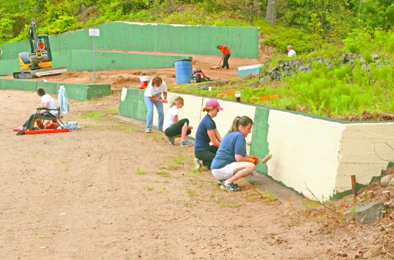 "Volunteer painters brighten the retaining wall at Babb's Beach as part of a big work crew on May 21. From far to near: Wendy LaMontagne, Kaci Seibert, Arielle Young, Lynn Joyal. The paint color, of course, was ""sand."" At the rear, Justin Ayotte, on a company bulldozer, prepares the upper beach at the rear with the help of more volunteers. No one went swimming, but Bailey Martin, a certified lifeguard, sat nearby just in case."