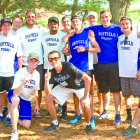 """Photographed on May 28 by the great Walter Camp Memorial Gate at Yale, the SHS Boys Tennis team emphasize their """"Number One"""" feeling after the CIAC tournament. From the left, standing: Matt Vindigni, Sam Pines (almost hidden), Brad PInes, Zach Pullen, Coach Mark Janick, Shlok Patel, Dwight Charkiewicz, Owen Gee, Brandon Armstrong, Tom Drakeley, Trustan Evans, Mike Parisi; in front: Peter Connolly, Zach Yahne."""