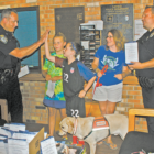 Holding one of the gift bags that Kayleigh Mahannah and Leah Beaudoin had brought to the Police Station, Officer Jeff Reynolds exchanges a high five with Leah. At the right are Amy Reay, who came with the girls, and Officer John Lacic, with another bag. That's Amy's service dog, Delancey, sniffing at the box of gift bags.