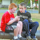 Noah Greico of Suffield and his friend Brenin Forbes of Windor Locks, both 10, share an iPhone playing Pokémon Go on the Suffield Green on July 22. The cannon they're sitting on is a Pokémon gym, where the game's monsters can compete.