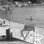 Beachgoers enjoy the water and the sand on a quiet, very warm Sunday afternoon in mid-July. The Town beach extends down to where the docks fill the shoreline along Middle Pond at Lake Congamond.
