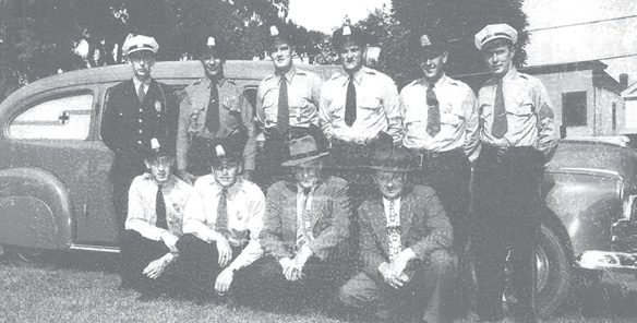 "The Suffield ambulance was originally staffed by members of the Police Department. Standing in front of the town's first ambulance, a 1946 Pontiac, are, from the left: Chief H. Hill, G. Hayes, M. Brockett, C. Sobinski, T. Zavisva, Sgt. J. Dineen. Crouching in front are: H. Sweatland, F. Leahey, Selectman H. Barnett, J. Boroski. The ambulance was known as the ""Blue Goose."""