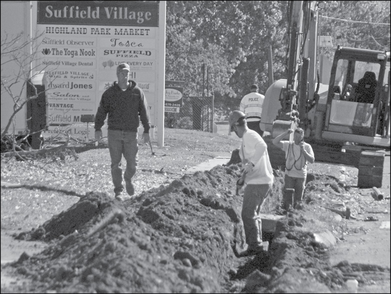 The trench for the extension of fiber optics connections among Suffield's municipal buildings is being dug down Bridge Street past the First National Bank in this October 10 photo.
