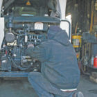 Grumbling about diesel on a cold winter afternoon in his equipment shed, an unidentified Suffield farmer changes the fuel filter on his Bobcat.