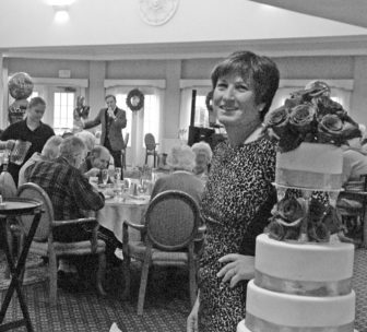 Suffield by the River proprietor Celia Moffie is pictured next to the birthday cake for the 18th anniversary of the facility on November 29.