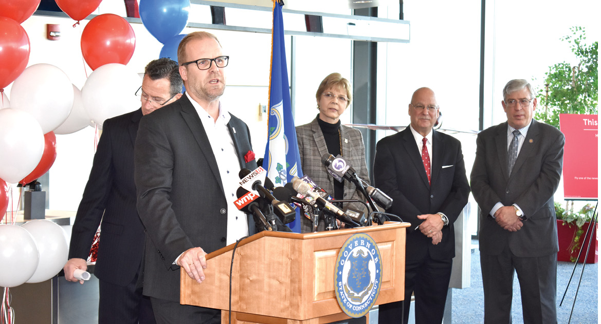 At Bradley International Airport on February 23, Lars Sande, senior vice president for sales of Norwegian Air International, responds to the welcome his company had received from Governor Dannel Malloy, partially hidden behind Sande. At the right are Suffield's Representative Tami Zawistowski, Executive Director Kevin Dillon of the Connecticut Airport Authority, and Representative Scott Storms of Windsor Locks. Amazingly, Norwegian Air's promotional fare one-way across the Atlantic (to Edinburgh, Scotland) is only $65.