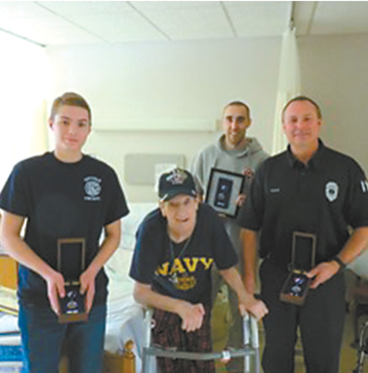 Members of the Suffield Fire Department who were honored for their valor are pictured at a recovery facility visiting the man they rescued. At left and right are Cadet Justin Seger and Lt. Kevin Seger; Firefighter Colby Tyler is in the rear.