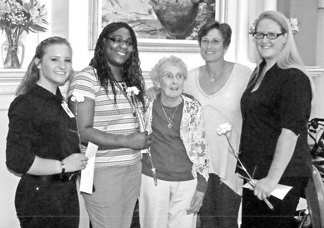 Althea Scheller, center, is pictured on May 3 at Suffield by the River with proprietor Celia Moffie and the three members of the residence's staff to whom she awarded scholarships.  From the left:  Jordyn Isabelle, Ansha Siawor, Mrs. Scheller, Moffie, and Kelly McInstrey.