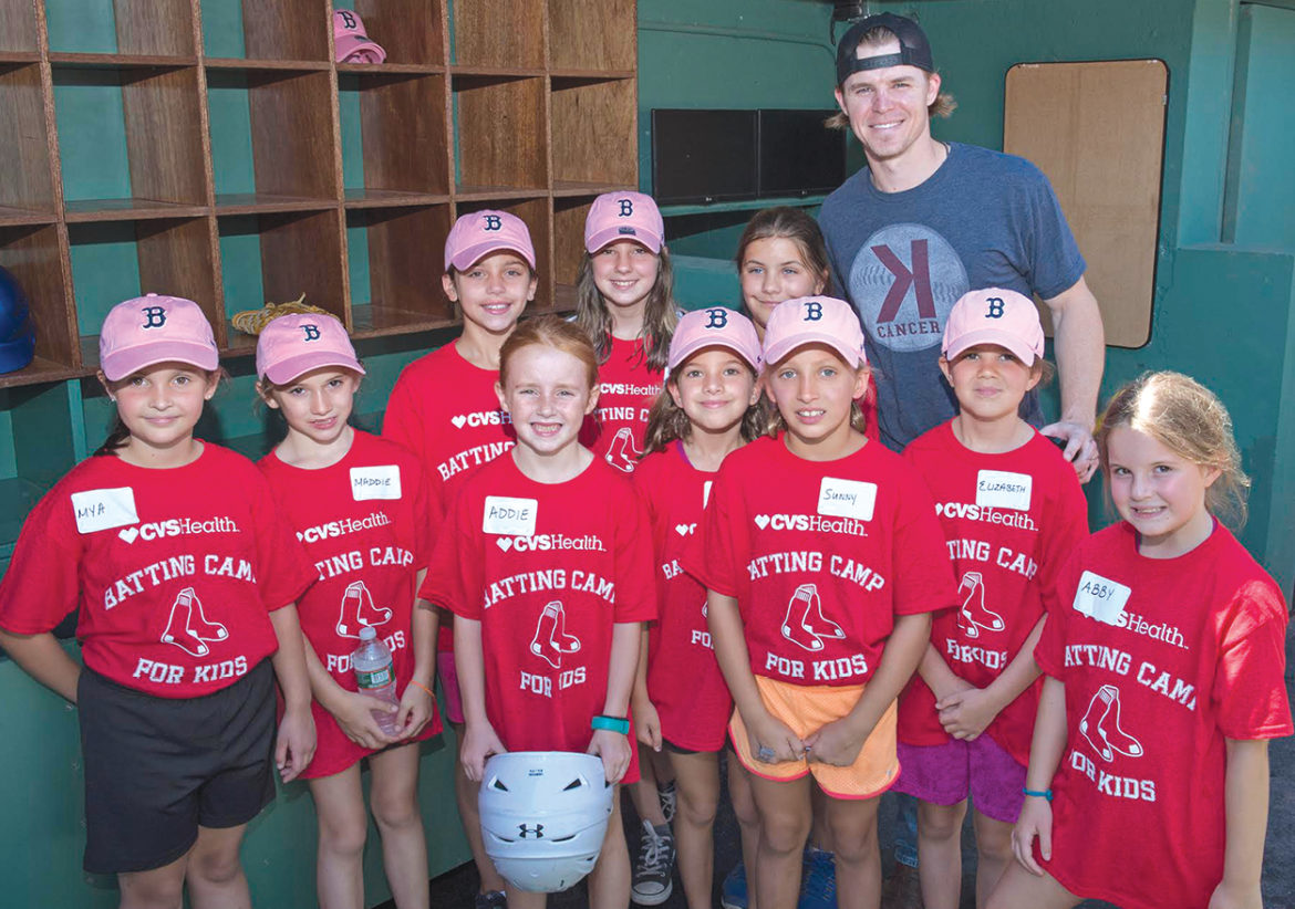 Boston Red Sox third baseman Brock Holt poses with players from the Pink Pugs Suffield Little League team. They were in the dugout at Fenway Park during a CVS Health Batting Camp. From the left, front row: Mya Johnson, Maddie Morello, Addie Holmes, Maddie Agrafojo, Sunny Sullivan, Elizabeth Strong, and Abby Caron. Rear Row: Charlie Morello, Ashlee Caron, Hannah Hadley, and Holt.