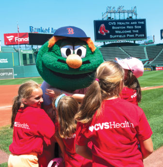 Mascot Wally the Green Monster engages happily with Suffield Pink Pugs players during their visit to Fenway Park, with a big Pink Pugs welcome emblazoned on the distant score board.