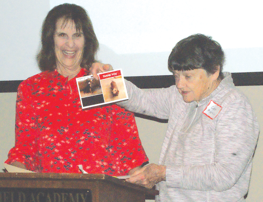 Associate Editor Carol Martin, right, holds up a Thank-you-for-our-rescue card from her dogs, which also conveyed thanks from the Observer staff, sent with the help of Managing Editor Ann Kannen. Both are inveterate dog-lovers.