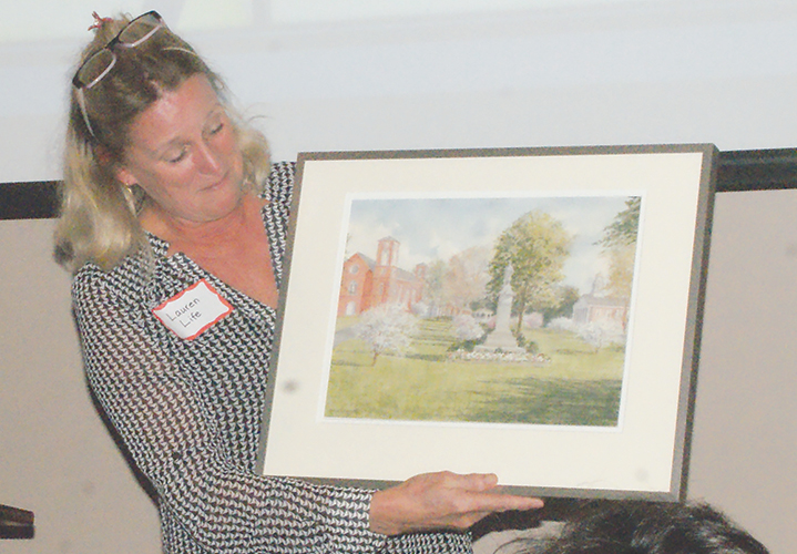 Lauren Life, now retiring as Chairman of the paper's Board of Directors, shows her thank-you gift, a print of Peggy MacKinnon's painting of the Suffield Green.