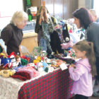 Jeannie Giauque tells Stephanie Garafolo and her daughter Giuliana how she knits the intricate specialties arrayed on her sales table at the Suffield Fire Department. The three-space garage had been emptied to make way for a wide variety of merchandise.