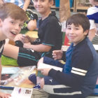 Friends enjoy newly purchased books from the annual fourth grade UNICEF book sale.