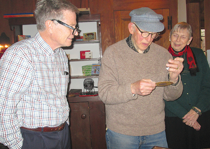 "At the King House Museum's annual Holidayfest on the first weekend of December, curator Lester Smith demonstrates ""Chiromagica"" to Chris Childs, left, and Jacquie Wadsworth. The mysterious 1905 game was one of the oldest in the event's special exhibit: ""Vintage Parlor Games."""