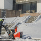 On Christmas Day, a snow removal contractor completes his task of clearing the morning snow from the sidewalks and the stairs of the Kent Memorial Library. Library patrons aren't yet welcome, but work continues in the buildng, and the paths are occasionally used for a shortcut from the Main Street sidewalk to Bank Lane.