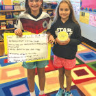Showing examples of the posters and collection banks they employed  to collect Florida hurricane relief are McAlister fifth graders Katelyn Allard, left, and Fiona Everett.