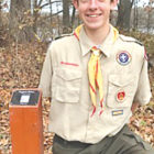 Eagle Scout Michael Sattan is pictured with one of the tree identification stations he designed and installed at Hilltop Farm.  The QR Code on a post near selected trees provides useful information about each tree.