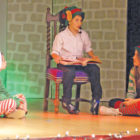 """Joseph Colangelo reads """"'Twas the Night Before Christmas"""" to an attentive duo of elves, Avaliese Hitchcock and Janine Eitel. The performance was one of the enjoyable acts of the Suffield Youth Theater's seasonal presentation on December 10."""