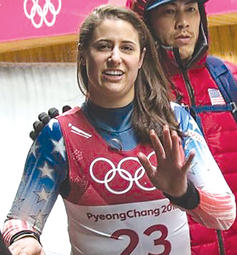 Emily Sweeney waves to her supporters after the crash as she is helped off the luge track by an Olympics staffer.
