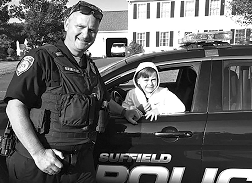 School Resource Officer Tom Kieselback is pictured during a neighborhood visit with an unidentified youngster in his patrol car.
