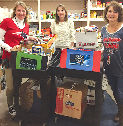 EAA Director Janet Frechette, center, happily accepts Food Bank donations brought from Spaudling School by Kris Pryce, left, and Denise Rigby.
