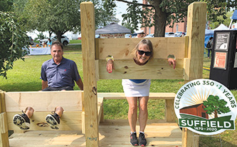 Mike Dukette in the stocks and Leslie Marx in the pillory suffer colonial punishment near the 350th Booth.